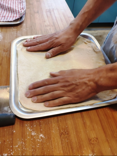 Pizza dough on baking sheet